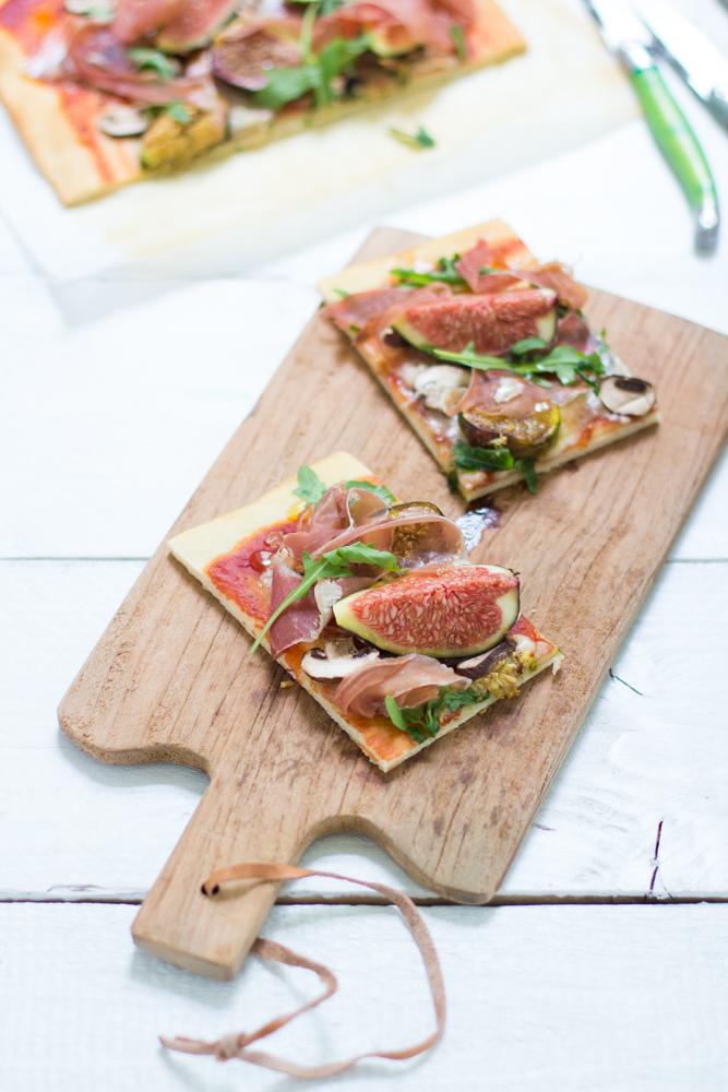 Pizza fine aux figues, champignons, jambon serrano, roquette, gorgonzola